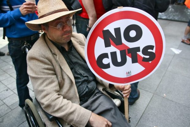 disabled-man-holding-no-cuts-sign-696x464